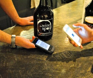 Using a digital wallet, a customer purchases a growler of beer using bitcoin at The Wine Spot. Photo credit: Rebecca E. Groynom